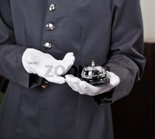 Hotelpage hält Glocke auf Hand