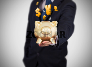 Businessman showing a gold piggy bank