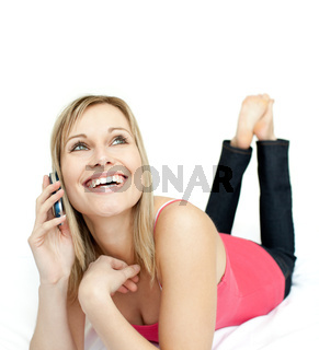 Jolly woman talking on phone lying on a bed