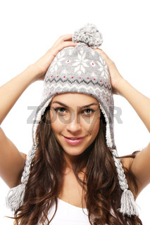schöne frau mit wintermütze hält arme über den kopf