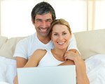 Smiling couple using a laptop lying in the bed