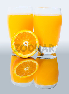A glass of orange juice with a half orange on a mirror