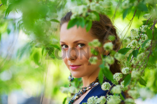Beautiful woman among blossoming trees