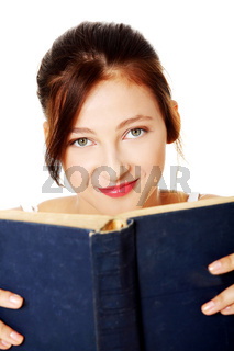 Closeup on young girl holding open book.