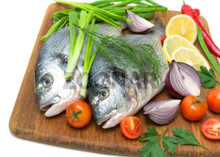 dorado fish with lemon and vegetables close-up on chopping board