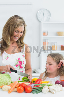 Mother preparing vegetable on the table in the kitchen