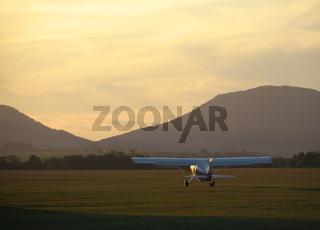 Motorflugzeug startklar vor Abendkulisse