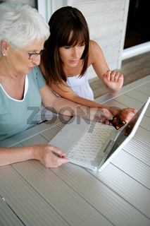 Young woman teaching her grandmother computer skills