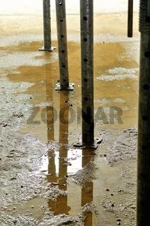 Stahlstützen mit Wasserspiegelung in der Baustelle