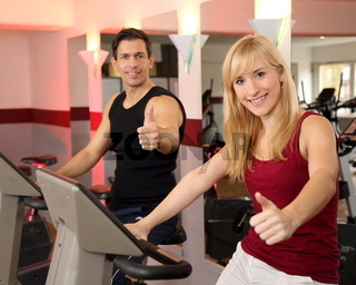 Attractive woman and a man cycling in a gym