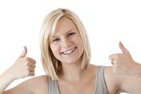 Sympathische blonde Frau hält lächelnd beide Daumen nach oben