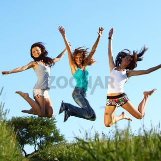 girlfriends jump in green grass field