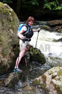 Wanderin mit Bergstöcken an einem Bergbach