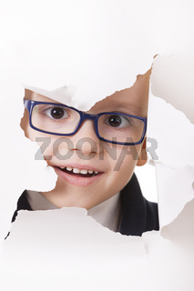 Curious kid looks through a hole in paper