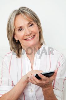 Lachende Seniorin benutzt Smartphone