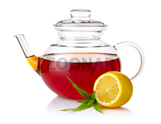 Teapot with black tea, green leaves and lemon slices isolated on white