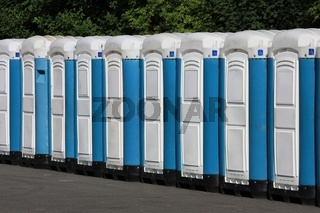 Row of mobile toilets in a summer festival area