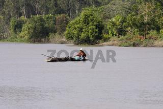 Eine Frau transportiert Flussgras in einem Kanu, Mekong Delta, Vietnam, Asien