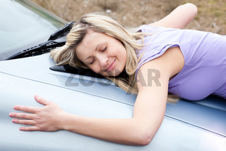 Cheerful female driver huging her new car