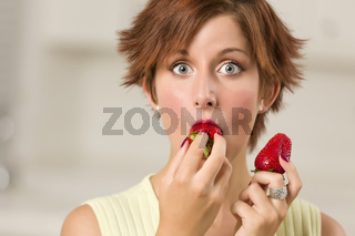 Pretty Wide-eyed Red Haired Woman Biting Strawberry