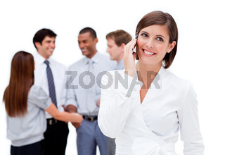 Brunette businesswoman on phone with her colleagues in the background
