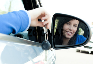 Cheerful teen girl sitting in her car holding keys