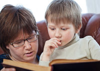 Boy and his mom reading book together