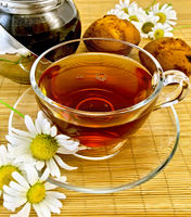 Herbal tea with daisies and kettle