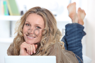 Smiling happy woman using a laptop