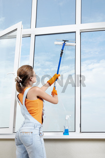 A young girl washes the window