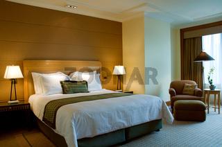 Elegantes Bett in geräumigem Schlafzimmer