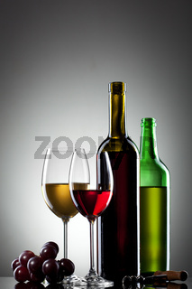 Red and white wine in glasses with grape and bottles