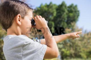 Boy looking through binoculars and pointing