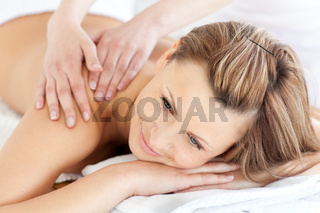 Positive young woman having a back massage in a spa center