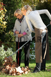 Young woman helping elderly woman to do gardening