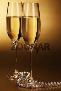 zwei gläser mit sekt und silberner kette