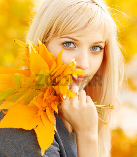 Autumn woman with yellow fall maple leaves