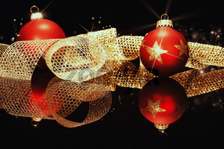 rote christbaumkugeln mit goldenem metallband