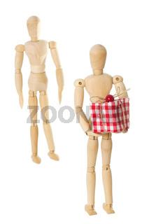 Eine Modellpuppe aus Holz die ein Geschenk hinter dem Rücken hält und eine andere Puppe vor einem weißen Hintergrund