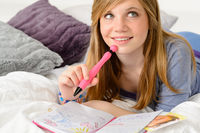 Daydreaming teenager girl writing her journal
