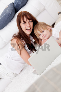 Happy young mother and her  daughter using a laptop