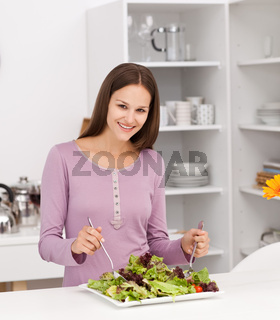 Pretty woman preparing a salad standing in the kitchen