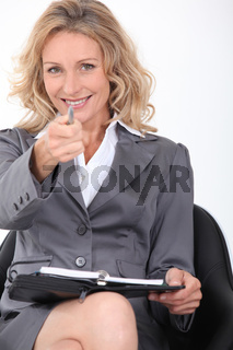 Smiling businesswoman pointing her pen  at the camera