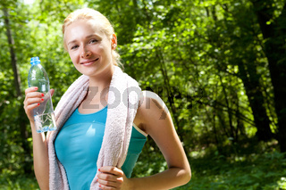 Portrait of beautiful smiling woman with bottle of water