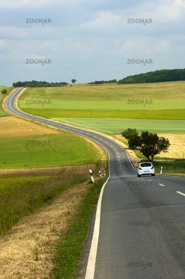 Landstrasse in Hügellandschaft mit Feldern