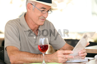 elderly gentleman seated in cafe drinking glass of red wine