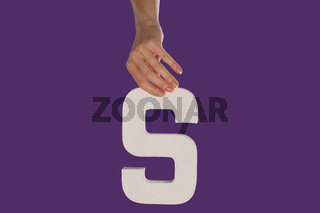 Female hand holding up the letter S from top