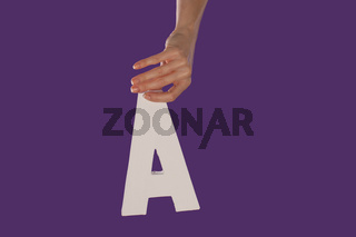 Female hand holding up the letter A from top