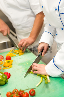 Close up of chefs cutting vegetables