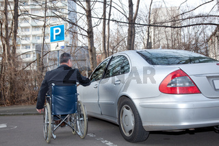 Mann im Rollstuhl neben Auto